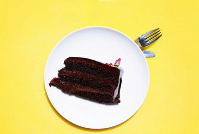 Thick slice of chocolate cake on a white plate on a yellow table