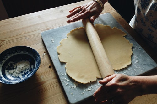 Baker using a rolling pin on pastry